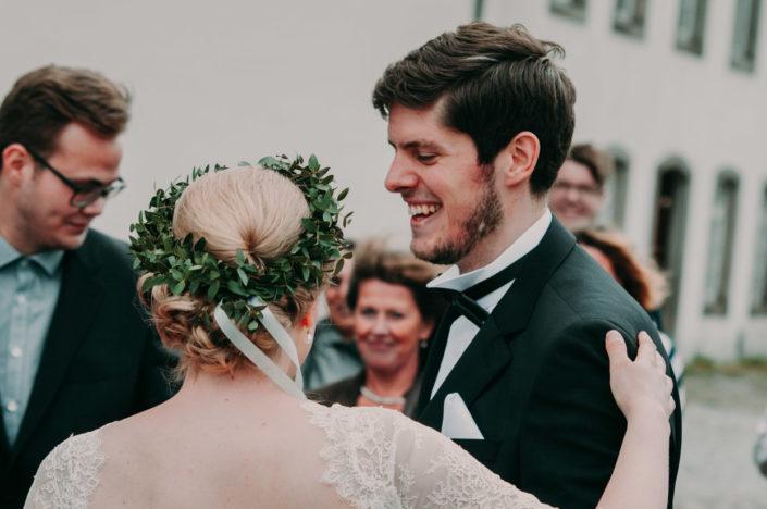 Braut und Bräutigam stehen lachend vor der Kirche