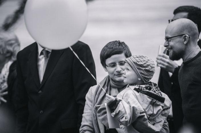 Eine junge Familie steht zusammen und hält einen Ballon