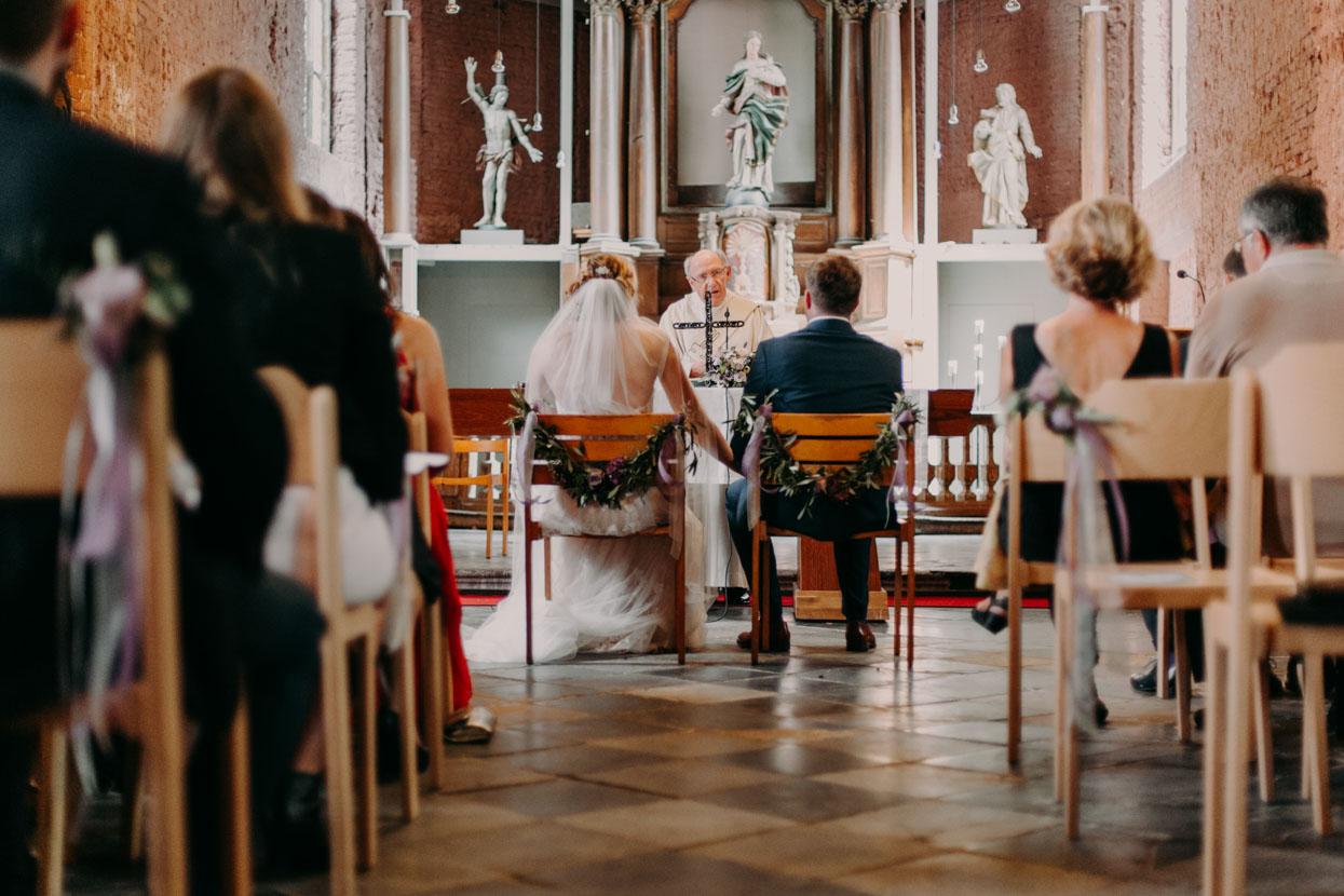 Der Pfarrer spricht am Altar zum Brautpaar