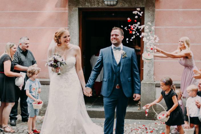 Das Brautpaar kommt im Blumenregen aus der Kirche