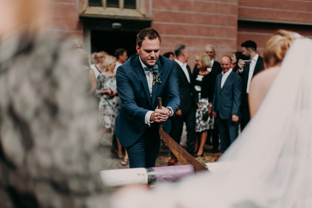 Der Bräutigam zersägt einen Baumstamm