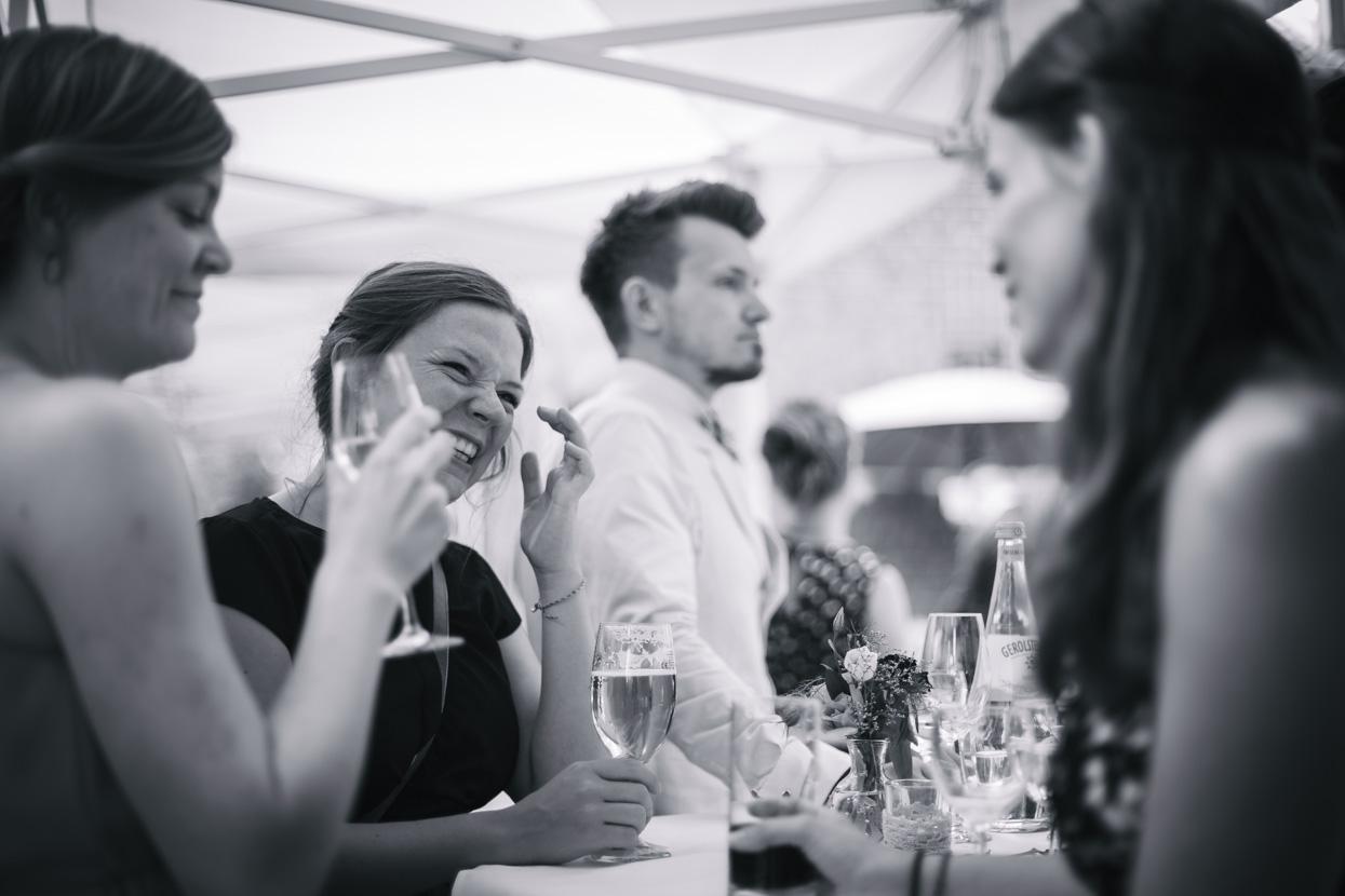 Lachende Gäste stehen am Tisch