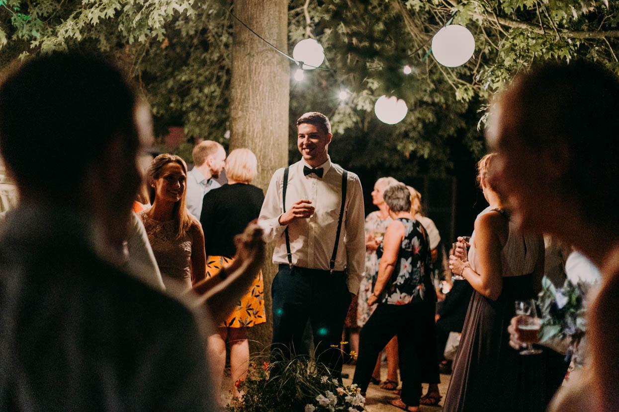 Gäste des Brautpaars stehen draußen an einem Baum