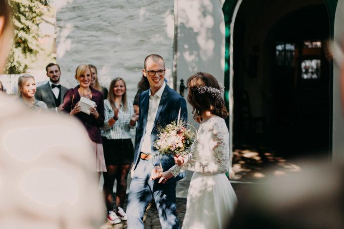 Das Brautpaar schaut sich vor der Kirche tief in die Augen