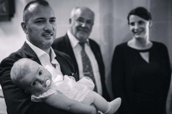 Nach der Taufe hält der Vater das Baby